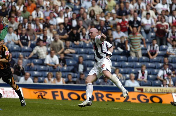 John Hartson lobs the 'keeper for his first Albion goal