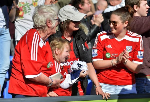 the travelling West Bromwich Albion Fans enjoy the match in the sunshine - one young fan holds tight the match shirt given to her by Chris Brunt of West Bromwich Albion