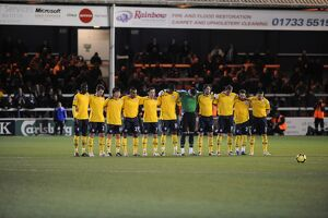 Team line up for the minute's silence before the game
